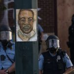 George Floyd hangs on a street light pole as police