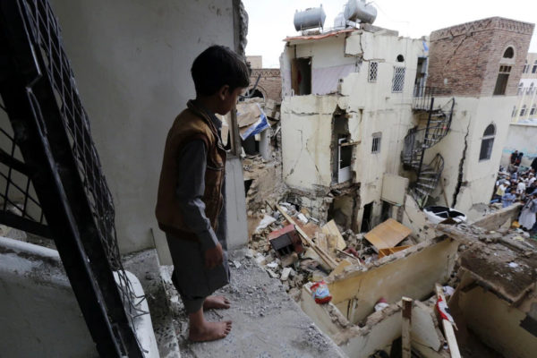 A Yemeni child looks at the ruins of war from a dilapidate structure