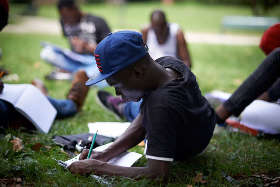 An unaccompanied foreign minor does lessons provided by a volunteer in a park in Toulouse, France, October 2017. Alain Pitton/NurPhoto via Getty Images