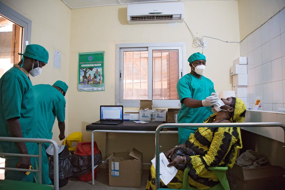 A healthcare worker performs a nasal swab as he tests a woman for COVID-19 in Bamako, Mali. Annie Risemberg/AFP via Getty Images